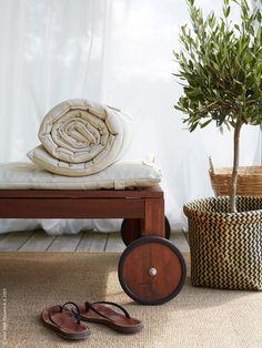 De krispigt vita VIVAN gardinerna bjuder på den perfekta skira skuggan i sommarrummet. ÄPPLARÖ solsäng med HÅLLÖ dynor, stor OSTED matta natur ramar in möbleringen. MAGGA korg.