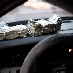 [pictured: two large wads of paper cash wrapped by two rubber bands sitting on a car dashboard]