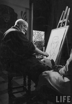 Gjon Mili: Artist Henri Matisse at his easel drawing from live model seated partially out of view; one of his stained glass panels in background. Nice, France, 1949.