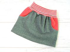 Girls green skirt made from heather green organic sweat and red and grey striped belly band The cozy and warm skirt is just as comfortable as the Kandatsu pants. Even with a skirt girls want to climb on playgrounds, ride a bike or jump over stones. The bellyband is elastic and aligns to the belly.  MATERIAL Heather green organic sweat Red-grey striped organic waist cuff (97% cotton, 3% elastane)  BETTER PANTS? I offer even pants in organic sweat. https://www.etsy.com/listing&#...