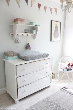 commode tegen grijsgroenige muur in de babykamer