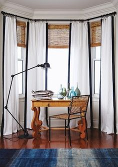 This is a good look for a bay window. Dress curtains edged in black, ties in with the black lamp and chair frame, and softens the wooden blinds