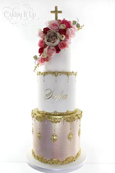 A striking romantic three tier christening cake. Bottom tier is hand painted with an antique silk lustre and embellished with ornate gold filigree details. Adorned with cascading flowers and gold fondant cake topper www.facebook.com/cakingitup