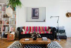 Sala de estar tem sofá chestefield preto com manta colorida, tapete com estampa étnica e mesa de centro de madeira.