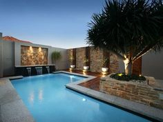 I love the mix of decking, paving stone. Water feature lovely mature tree. Striking pool zone