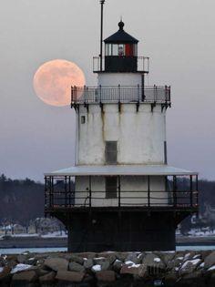Luna llena se eleva detrás de la casa Luz Spring Point en South Portland, Maine