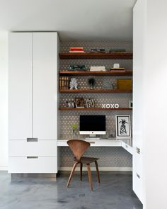 This corner home office makes ample use of a small space with built-in shelves and two sleek white cabinets with a matching desk. Gray and white geometric wallpaper lends a funky, midcentury modern vibe, while polished concrete floors complete the look of the space.