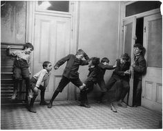 ca. 1902, [two boys fighting and two boys pushing on door through which a school teacher is trying to enter], Fitz W. Guerin