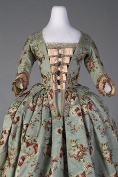 This matching bodice and skirt dates to around 1765. The textile is a magnificent brocaded silk. The close-up photographs give a sense of the texture of the ribbed silk and the brocaded floral patterns. The stomacher with the peach bows is a reproduction, which the Museum Director Jean Druesedow created from silk which she carefully dyed to match and ribbons. Front 1 Kent State University Costume Museum