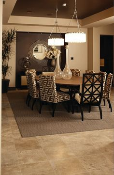 Combining stone tile flooring with a coordinating area rug adds a touch of layering that is so popular for modern and traditional homes.  https://www.barronsflooring.com