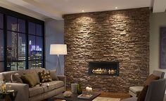 Accent stone living room wall with mini firepit and big open windows...dream!