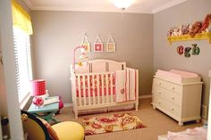seriously LOVE the gray walls with white wood and bright yellows, oranges and pinks in this nursery.