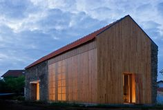 Portuguese architect João Mendes Ribeiro has transformed a rustic barn in Cortegaça into a sprawling modern home. Embracing the minimalism of the historic façade, the barn was converted into an airy sun-drenched residence. Wooden louvers and a built-in mezzanine maximize light and space, making the house open yet comfortable. The resulting home meshes modernity with the original layout of the barn, creating cozy sleeping areas while utilizing the double height of its rustic past.