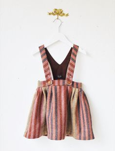 Inspired by my daughter and my background as a textile artist I have produced a range of alternative style baby clothes. I wanted to use designs and colours which were not your average for babies and to toddlers.  This 100% wool skirt is perfect for Autumn/Winter with its English tweed feel it has beautiful shades in a herringbone style stripe. It has a fine cotton lining and underskirt. With its unique full shape it looks great with a pair of coloured tights. The waistband has an overla...