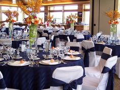 Banquet room set up with navy blue overlays and orange center pieces.