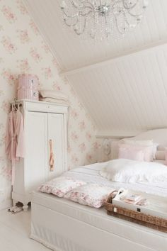 Cottage bedroom with delicate floral wallpaper contrasting the white tongue and groove walls