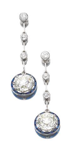 SAPPHIRE AND DIAMOND PENDENT EARRINGS, CIRCA 1920 Each circular-cut diamond within a calibré-cut sapphire border, to a line of three collet-set circular-cut diamonds, screw back fittings.
