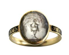 This mourning ring features a sepia painting of an urn on ivory, surrounded by weeping willows made of tiny pieces of hair