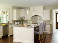 This neutral kitchen mixes classic, tailored pieces like upholstered barstools from Restoration Hardware with sleek, updated touches like pearly Ann Sacks subway tile. A large island with barstools creates a casual eating area beneath elegant glass pendant lighting.