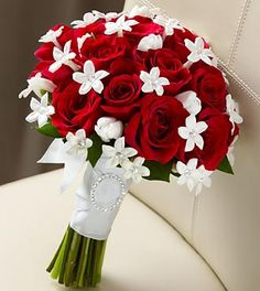 """The FTD® Poetry™ Bouquet has a look of pure elegance and charm that will make you look your bridal best. Red roses are accented with white tulips and white stephanotis blooms, beautifully tied together with a white French taffeta ribbon to give you an appearance that only poetry could describe. Approximately 13""""H x 10""""W."""