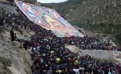Turistas e peregrinos se reúnem ao lado de uma imagem gigante de Buda no monastério de Drepung, em Lhasa, no Tibete