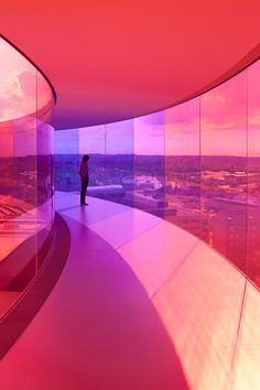 """""""Your Rainbow Panorama"""" is a Rainbow-coloured glass walkway on the roof of the Danish art museum ARoS Aarhus Kuntsmuseum, by Danish-Icelandic artist Olafur Eliasson. The permanent piece consists of a 150-metre-long and three-metre-wide self-contained circular walkway with glass that moves through all of the colours of the spectrum. The 52-metre-diameter walkway """"floats"""" 3.5 metres above the roof and stretches like a multi-coloured halo — supported by 12 slender columns. The piece opened to…"""