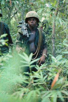Um, jovem M60 operador de metralhadora de alerta na selva. Nomes, data e local desconhecidos.