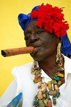 Havana, Cuba - woman with a cigar. Black woman. Afro-Cubana. Cigar. Baubles, jewels. Blue, yellow, red, white. Stunning contrast. Great pose. FACE!