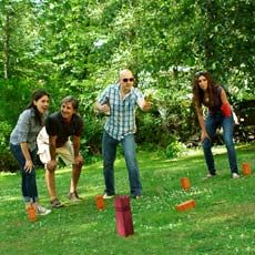 four people playing kubb in yard