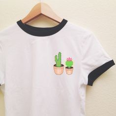 """Our super soft ringer tee,featuring contrasting black neckline and sleeve  bands,with our """"Cactus"""" graphic on the left chest. Our ringer tees are a  staple to any girl's closet, adding a touch of grunge. They look great  styled casually with jeans and boots, or dressed up with a cute plaid  skirt.  ONLY AVAILABLE IN SIZE SMALL, PLEASE CHECK SIZING !Unfortunately, we DO  NOT have any stock in Medium or Large. Thank you for being understanding.  Description :  100% Combed Cotton  Small…"""