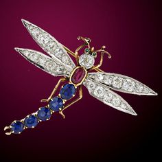 An outstanding gem encrusted dragonfly brooch, circa 1900. This playful pin twinkles with 4.00 carats of old mine cut diamonds and 4.00 carats of high quality oval cut sapphires. The platinum over gold pin is finished with a bright ruby set into the body and emerald colored cabochon eyes.