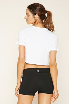 """An athletic knit crop top complete with short sleeves, rolled trim, and a hem """"Believe"""" graphic."""