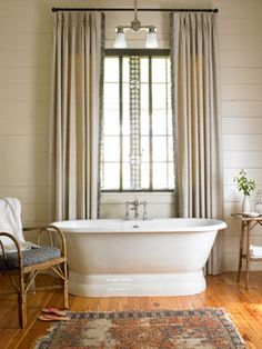 In the master bath of this summer cabin, a thrift-shop rattan chair cozies up to the vintage tub
