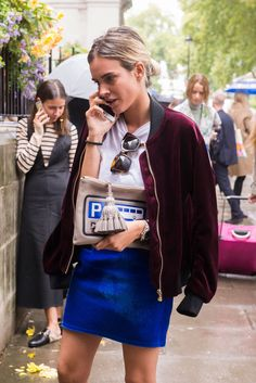 A velvet bomber, bright blue skirt, and a graphic clutch