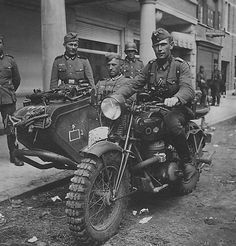 Wehrmacht sappers put to immediate use captured Belgian motorcycle Gillet-Herstal AB-720. This was a sturdy bike with a (surprisingly) two-stroke engine. Manufactured for both the Belgian and the French armies, it saw service in WW2 mainly in German hands. Note the super heavy side car; the contraption in front of the passenger is a multifunction support for weapons or other gear. This particular bike wears heavy duty cross country tires. The front system has no shock absorb save a large…