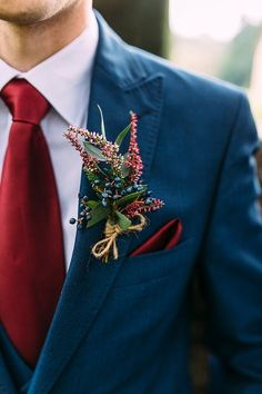Blue Wedding Suit With Red Accents: From a red tie or bow tie, to a pocket square, a vest, or even socks, there are plenty of accessories that the groom can use to show that he's on board with the wedding theme. | Gorgeous Ideas for a Red Wedding Palette