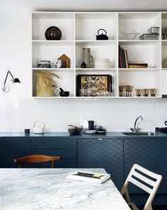 We love the combination of these gorgeous blue cabinetry, bright white tile and open shelving.