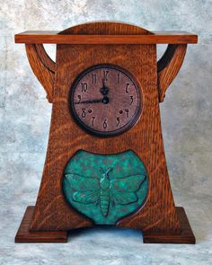 Arts & Crafts style clock with a ceramic moth tile. Made of quartersawn white oak. Etched and hammered copper face. Hermle mechanical movement. Dye finish hand rubbed with tung oil and waxed with dark brown Briwax.