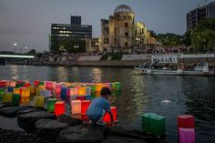 A boy floats a candle lit paper lantern on the river in front of the Atomic Bomb Dome  during 70th anniversary activities, commemorating the atomic bombing of Hiroshima at the Hiroshima Peace Memorial Park, on Aug.6, 2015