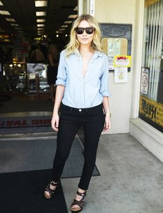 Ashley Olsen wears a blue button-down blouse with black skinny jeans, platform sandals, a gold watch, and Ray-Ban sunglasses