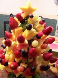 Fruit Tree I made for our ladies Christmas brunch.  Use a Styrofoam cone, cover it with lettuce secured with floral pins, Place fruit on skewers and stick in the cone.  The star is cut from cantaloupe using a cookie cutter.