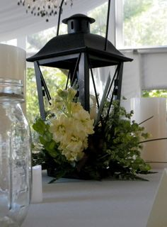 With the black crystal chandelier and mason jar glasses the rustic look of the lanterns was a great choice. — at Briarwood Florist.