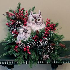 Wintery owls make are the center of this beautiful winter arrangement. I have added red berries, pine greenery, pine cones, and green berries with greens.