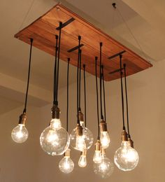 Handmade chandelier light fixture has industrial feel. Made from reclaimed hardwood floor found at Build It Green NYC. Includes vintage look bulbs. Original boa