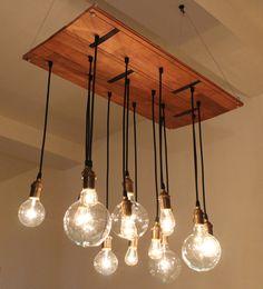 Handmade chandelier light fixture has industrial feel. Made from reclaimed hardwood floor found at Build It Green NYC. Includes vintage look bulbs. Original boa