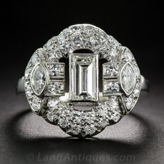 Art Deco Diamond Ring - This singular and stunning Art Deco sparkler - circa 1920s-30s - features a glistening half-carat baguette diamond, seemingly floating in the center of a puffed cushion of glittering pavé-set diamonds further embellished with an old mine marquise diamond