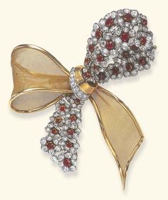 A RUBY, DIAMOND AND GOLD BOW BROOCH Designed as entwined ribbons, one of sculpted gold mesh, the other decorated with circular-cut ruby and diamond florets, gathered by a circular-cut diamond and polished gold ribbon, mounted in platinum and gold, circa 1955.