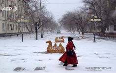 A picture taken on November 16, 2016 shows a woman walking along a street during a snowfall in Baikonur, Kazakhstan. Central Asia's Kazakhstan was hit by unusually cold weather, with temperatures in some areas dipping 30 degrees below the season's...