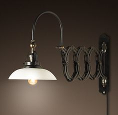 """1950s Factory Scissor Sconce    Dating to l950s Italy, this mid-century scissor sconce was designed for factory illumination. We've reproduced it for the home, enamored of its inventive looks, white glass shades and accordian mechanism that expands up to 40"""" in length to offer light wherever needed.    Hide product details...        Built of stamped steel      Bronze finish      White glass shade      Accordion mechanism adjusts to position light where needed      Plug-in  For an upstairs…"""