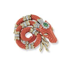 A coral, diamond and emerald brooch, by David Webb. Designed as a carved coral ram's head #christiesjewels